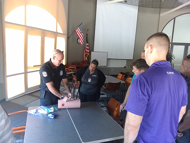 A paramedic shows EMCC employees how to use a tourniquet to stop the bleed.